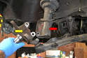 With the bolts removed you can slip the strut (red arrow) out from the spindle (yellow arrow).