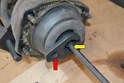 If you do not have an impact driver insert a 7mm Allen into the top of the strut shaft (yellow arrow) and use a 22mm craw foot wrench (red arrow), the type you would remove an O-2 sensor with to remove the nut.