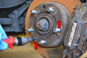 Set the parking brake and loosen or remove the two Philips head screws that hold the rotor to the flange (red arrows).