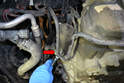 Use a 13mm wrench or socket and remove the nut holding the power steering bracket on (red arrow).