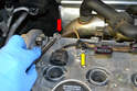Next remove the 10mm ground wire connection (red arrow) and slide the wiring harnesses plastic retainers out of the valve cover (yellow arrow).