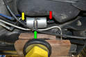 Move to under the car where you will see the filter held in place by a bracket (green arrow) that also holds two other lines and the input (red arrow) and output (yellow arrow) fuel lines.