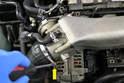 Begin by using a flathead screw diver and removing the clamp (yellow arrow) holding the intake hose to the throttle body.