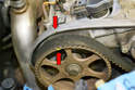 Rotate the engine until the cam chain sprocket is lined up with the witness mark on the sprocket and the head (red arrows).