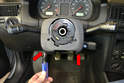 With the steering wheel removed you start by removing the upper trim piece. The upper piece is held in place from below by two Philips head screws.