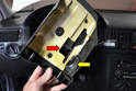 Lower the trim panel taking care to clear the adjustment handle through its opening (red arrow) and that you do not tear the rubber gasket (yellow arrow) around the ignition switch opening (yellow arrow).