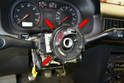Release the three plastic clips (red arrows, two shown) holding the slip ring to the steering column.