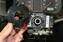 Slide the slip ring (red arrow) off the steering column.