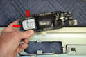 Now you have a much better angle to gently pry the small clips and tabs (red arrows) holding the switch in the housing.