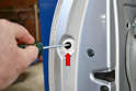Once the grommets are removed, you will see a small T20 Torx screw.