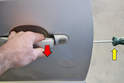 Hold the door handle in the out position (red arrow) while loosening the T20 screw (yellow arrow).