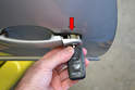 Slide the lock tumbler out from the door (red arrow).