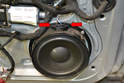Unplug the connection from the speaker by squeezing in the two clips (red arrows) and pulling straight out.