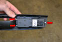 Flip the unit over and remove the three Philips head screws (red arrows) holding the switch assembly in place.