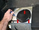 Remove the three Philips head screws (red arrows) holding it in place and gently pry the panel up.