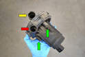 With the pump removed from the vehicle you can see the inlet opening (yellow arrow), pressure opening (red arrow) and the rubber isolating bolts (green arrows).