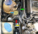 The power steering reservoir (red arrow) is located in the front right side of the engine compartment between the coolant overflow reservoir and the windshield washer reservoir.