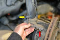 Begin by disconnecting the brake pad wear sensor from the harness (red arrow) and unclipping the wire from the holders on the strut (yellow arrow).