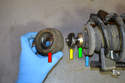 Remove the suspension mounting bushing (red arrow), spacer (yellow arrow), bearing (green arrow) and the spring seat (blue arrow).
