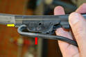 Slide the blade (yellow arrow) towards back out of the loop in the wiper arm (red arrow).