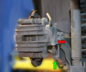 You will need to remove the parking brake ball end (red arrow) and cable clip (green arrow).