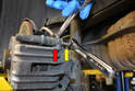 Use a 15mm wrench to counter hold the guide pins (red arrow) while removing the 13mm bolts (yellow arrow).