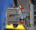You will need to remove the two 13mm bolts from the caliper (red arrows).