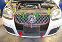 The front grill on the GTI MkV is held in by two T25 Torx screws (yellow arrows) on top, two T20 Torx screws (red arrows) and two clips (green arrows).