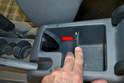Open the arm rest compartment and use a trim removal tool to open the forward plastic piece (red arrow).