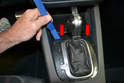Use your trim removal tool and gently pry the front of the shifter trim panel up and towards the rear (red arrow).
