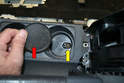 Remove the rubber insert (red arrow) at the bottom of the rear cup holder and remove the T20 Torx screw (yellow arrow).