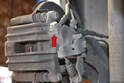 The fitting on the caliper is the same as the fitting to the caliper on the front (red arrow).