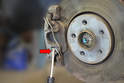 Place a large flat head screwdriver between the caliper and retaining clip (red arrow).