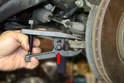 Depending on the age and condition of the tie rod end you may need to use a pickle fork or ball joint remover (red arrow) to separate the ball joint from the bearing housing.