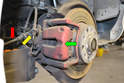 The caliper (green arrow) has the parking brake line (red arrow) and brake line Yellow arrow) attached to it.