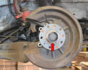 With the rotor off begin by using a flathead screwdriver and prying off the dust cap (red arrow).