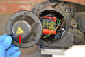 Remove the headlight access cover from the rear (red arrow) by turning it counter clockwise and pulling it off the housing.
