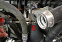 Use a flathead screwdriver and loosen the clamp on the throttle body hose (red arrow).