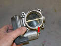 Use some carburetor cleaner and give the throttle body and valve a good cleaning (red arrow).