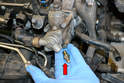 Use a 13mm wrench and remove the Schrader valve from the pump body (red arrow).