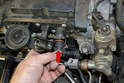 Remove the crankcase vacuum line behind the manifold line (red arrow).