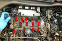 Loosen the fourteen T30 screws holding the valve cover in place (red arrows).