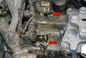 Remove the old cooler from the mount using care not to spill the coolant in the actual cooler into the transmission openings (red arrows).