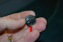 This photo illustrates one of the plastic retaining screws (red arrow).