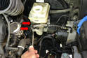 Remove the two brake lines attached to the right side of the master cylinder (red arrows).
