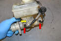 If you are reusing the lines and reservoir, begin by removing the two supply lines (red arrows, if still attached) from the master cylinder.