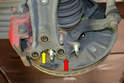 Lift up the steering knuckle (red arrow) and lower the control arm (yellow arrow) to separate them.