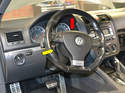 Using the steering column adjustment and pull the steering wheel away from the dash (yellow arrow) and lower it as far is it will go (red arrow).
