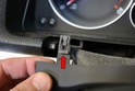 This photo illustrates the small clips that hold the trim piece in place (red arrow).