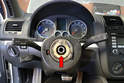 You will need to remove the steering wheel (red arrow) to get access to the trim panels around the steering column.